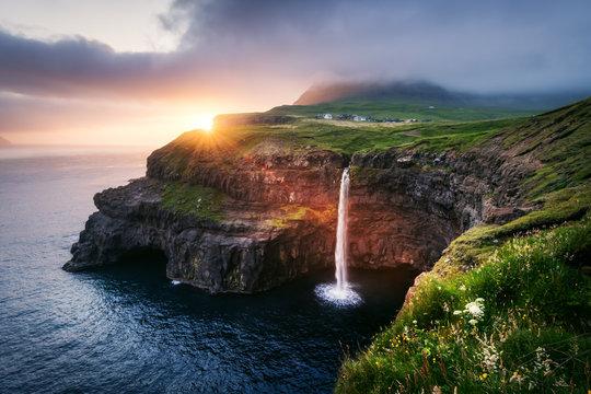 Incredible sunset view of Mulafossur waterfall in Gasadalur village, Vagar Island of the Faroe Islands, Denmark. Landscape photography