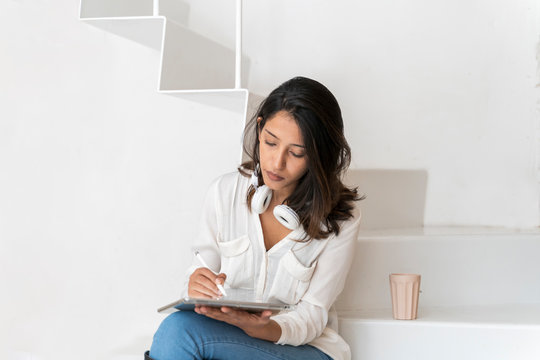 Portrait of young architect sitting on steps in a studio working on tablet
