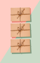 Three eco-friendly presents in a cardboard boxes decorated with a rope bow on green and pastel pink background