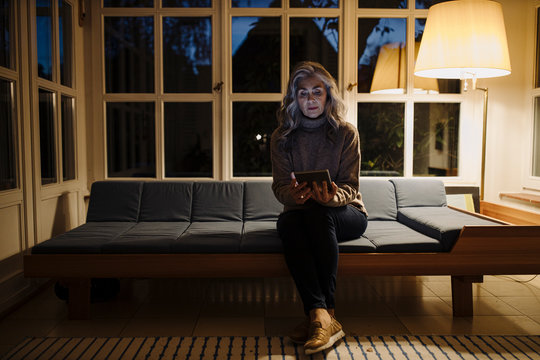 Mature woman using tablet on couch at home in the dark
