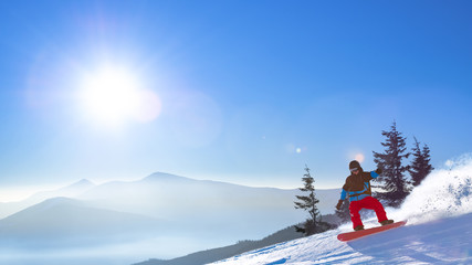 Snowboarder Riding Red Snowboard on the Slope in the Morning Mountains at Sunny Weather. Snowboarding and Winter Sports