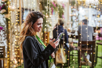 Portrait of happy young woman at fair using cell phone Wall mural