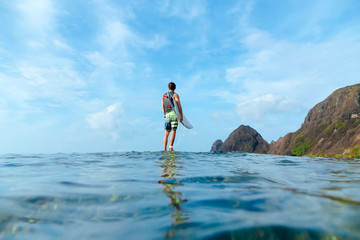 Surfer holding his surf board, standing on stone, Sumbawa island, Indonesia, over-under image