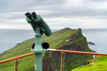 Foggy view of old lighthouse from viewpoint with tourist binoculars on the Mykines island, Faroe islands, Denmark. Landscape photography