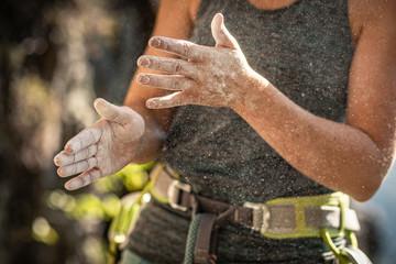 Woman preparing to climb, using chalk powder