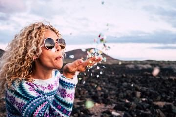 Blond woman blowing confetti in the air, Tenerife, Spain