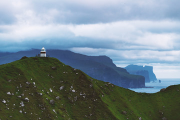 Panorama with Kallur lighthouse on green hills of Kalsoy island, Faroe islands, Denmark. Landscape photography
