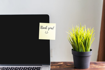 Thank you note on laptop screen, natural light.