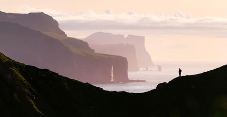 Man silhouette on background of famous Risin og Kellingin rocks and cliffs of Eysturoy and Streymoy Islands seen from Kalsoy Island. Faroe Islands, Denmark. Landscape photography