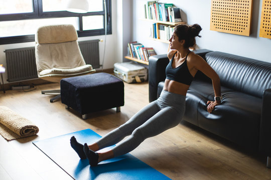 Fitness workout at home. Healthy fit young woman doing triceps dips exercise in the living room.