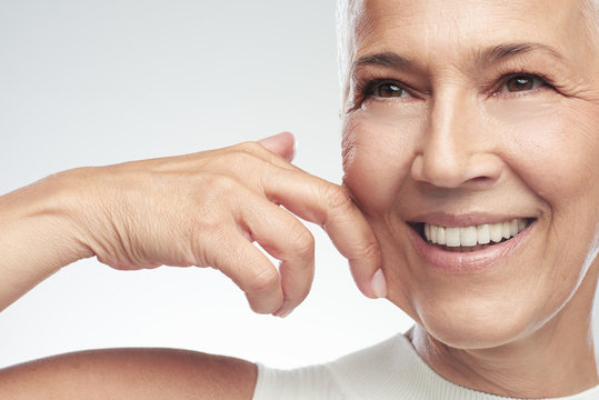 Gorgeous smiling Caucasian senior woman with short gray hair pinching her cheek. Beauty photography.