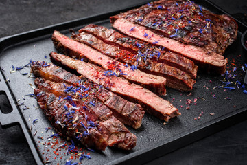 Modern design barbecue dry aged wagyu flank steak offered with herb and salt as closeup on a modern design tray