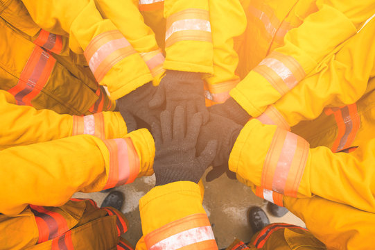 Firefighter putting hands up for fire fighting, Cheerful people giving strength motivation. Teamwork concept