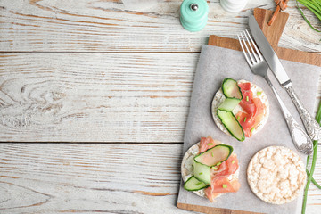 Puffed rice cakes with prosciutto and cucumber served on white wooden table, flat lay. Space for...