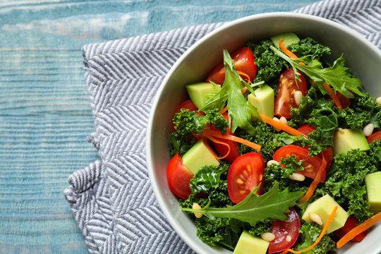 Tasty fresh kale salad on light blue wooden table, flat lay