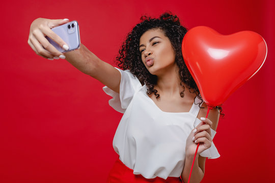 beautiful black woman making selfie on phone with heart shaped balloon isolated over red