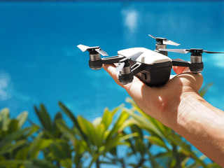 Start the drone, launching from hand. Swimming pool and garden background. Copy space.