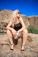 Fotobehang Young blonde in dark glasses on granite stones