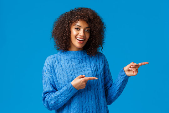 Hey visit this site. Cheerful happy african-american female in winter sweater, inviting check-out holiday prices and special discounts, pointing fingers right side and smiling, blue background