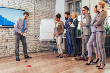 Respectable elderly man in a business suit playing mini-golf in his office. Nearby are his assistants and watching