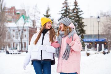 Two happy beautiful girlfriends walk in the winter in a city park