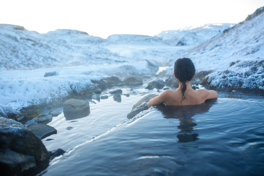 The girl bathes in a hot spring in the open air with a gorgeous view of the snowy mountains. Incredible iceland in winter