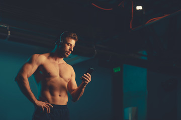Fototapeta Shirtless young athletic man chooses music for workout in the underground garage obraz