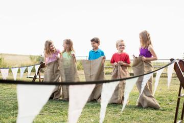 Kids lined up to start a potato sack race.