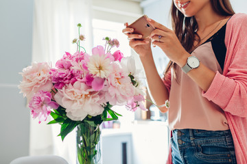 Womens day, Valentines day present. Woman taking photo of bouquet of peonies flowers. Gift from husband