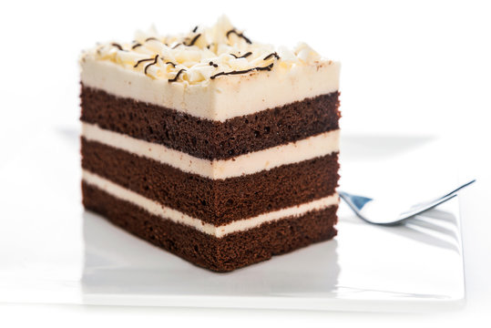 Delicious multilayer homemade cocoa sponge cake with sugar mass on a plate with a fork in close-up