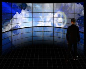 Man before video screens with binary code stream