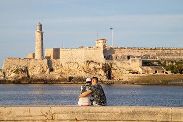 A pair of guys in love cuddle on the seafront of Malecon, Havana, Cuba