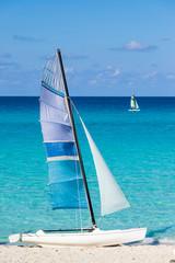 Speed Sailing catamaran on the beach. Two catamarans and a sail boat on tropical beach.