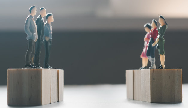 miniature men and women stand on wooden cube confront each other
