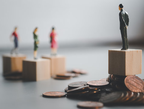 gender gap, difference income between man and woman, miniature man and woman stand on coin stacks