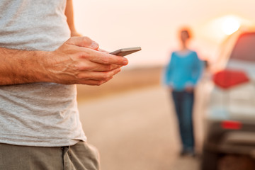 Man texting for roadside assistance after vehicle broke down