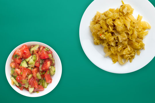 stewed cabbage in a white plate on a colored background. stewed cabbage top view. healthy eating. vegetarian food .