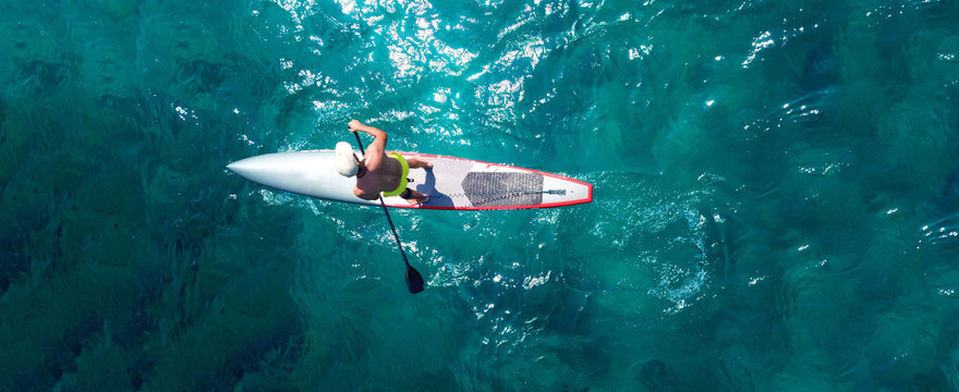 Aerial drone top down ultra wide photo of man practising in Stand Up Paddle or SUP board in tropical exotic sea