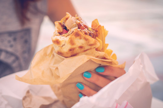 Close up on the pita gyros in the hands of young caucasian woman holding eating in sunny summer day
