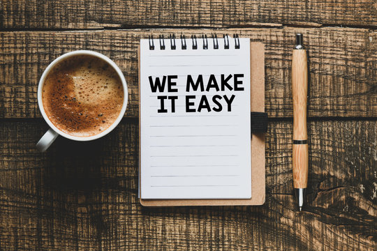 We make it easy text in the notebook on a wooden table. Top view - business concept.