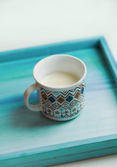cup of milk stay on wooden painted tray