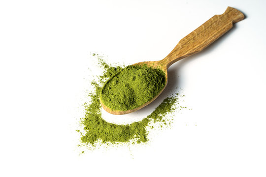 Matcha green powder in wooden spoon isolated on white background