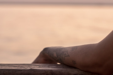 a good looking partial closeup shoot to tattooed girl arm - blurry sea as background