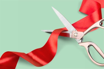 Scissors cutting the red ribbon on pastel background