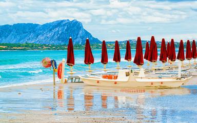 Landscape with umbrellas on La Cinta beach and Mediterranean Sea and Tavolara Island in Sardinia on Italy in summer. Scenery view on Sardinian beach in Sardegna. Olbia province. Mixed media.