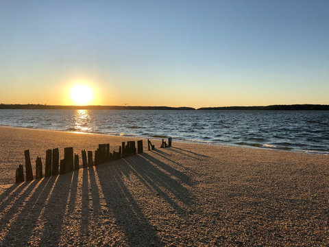 Sunset over Hobart Beach Park with remnants of a wood fence in Northport, Long Island, New York.