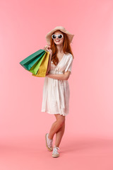 Full-length vertical shot feminine, relaxed and elegant redhead female in sunglasses, straw hat and...