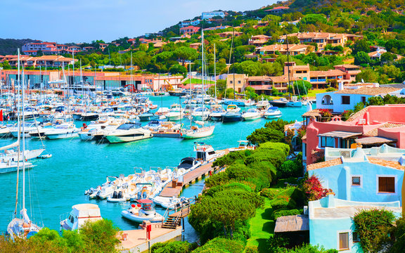 Scenery with Marina and luxury yachts at Mediterranean Sea of Porto Cervo in Sardinia Island of Italy in summer. Landscape View on Sardinian town port with ships and boats in Sardegna. Mixed media.