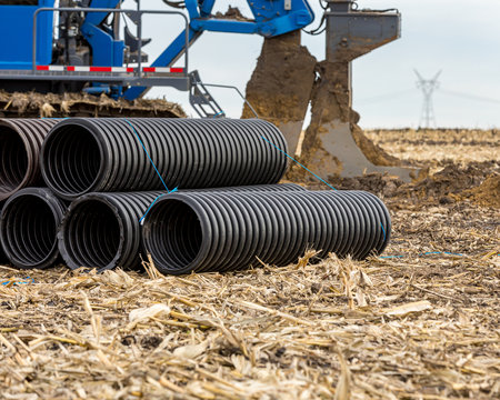Black corrugated water drainage pipe, field tile, in farm field with tile plow or ditcher in background