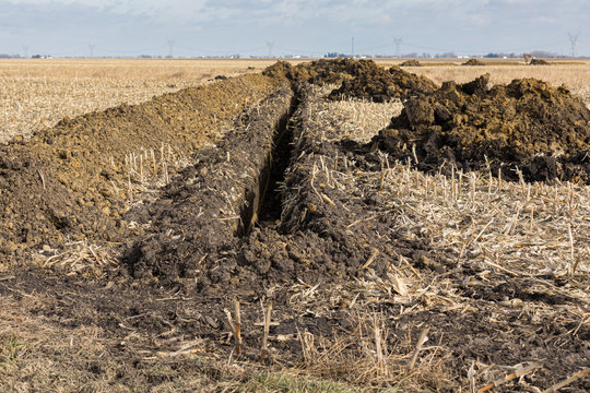 Trenck excavated in farm field with piles of soil. Water drainage pipe, field tile, installation